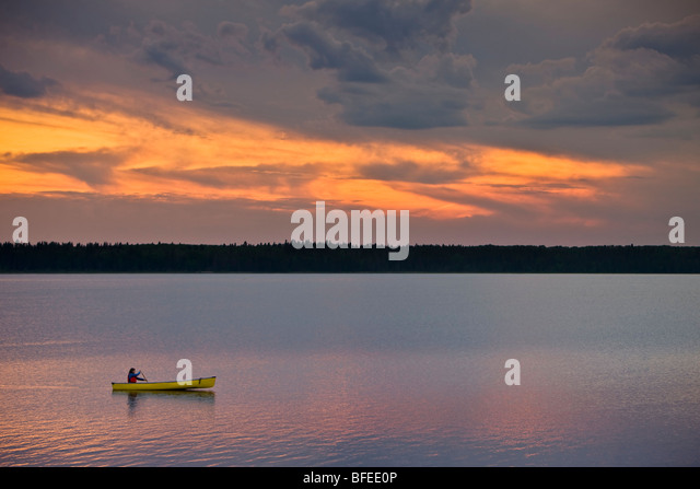 Canoeing on Lake Audy at sunset in Riding Mountain National Park, Manitoba, Canada - Stock Image