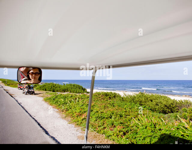 Tourists riding golf carts on Rueda Medina, a main road that runs from Playa Norte to Punta Sur in Isla Mujeres,Mexico - Stock Image