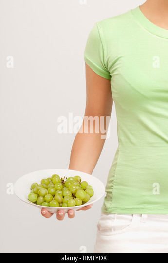 Mid section view of a woman holding a bowl of grapes - Stock-Bilder