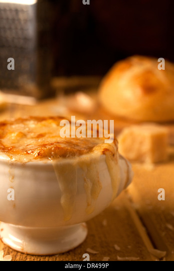 French onion soup with grated cheese and a round loaf of French bread - Stock-Bilder