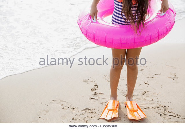 Girl in inflatable ring and flippers on beach - Stock Image