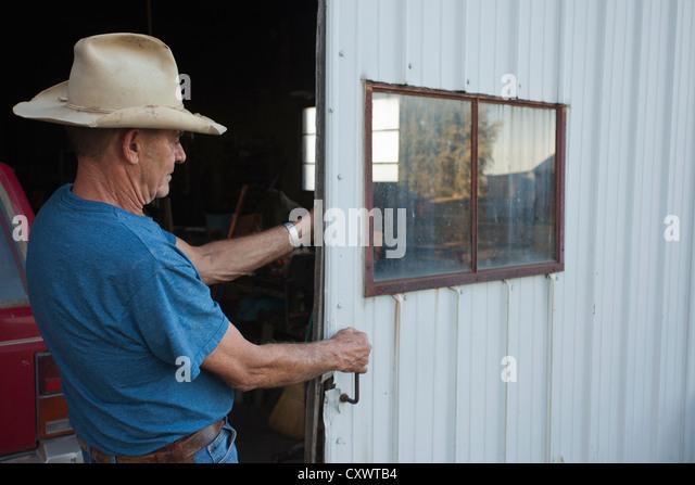 Farmer closing sliding garage door - Stock Image