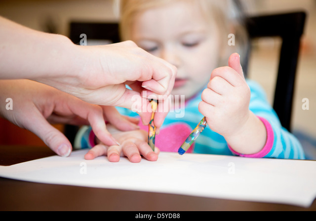 Girl Drawing with Mother - Stock Image
