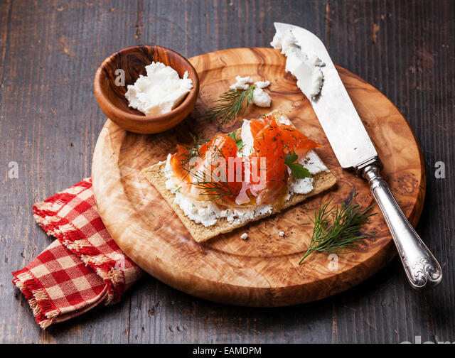 Sandwich on Crisp bread with Smoked salmon and soft Cream cheese on Olive wood plate - Stock Image