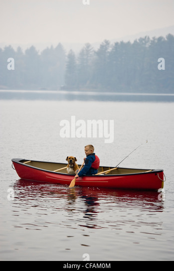Young boy going fishing with dog in canoe on Source Lake, Algonquin Provincial Park, Ontario, Canada. - Stock Image