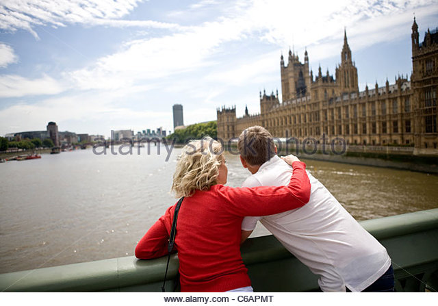 A middle-aged couple standing near the Houses of Parliament, looking along the river Thames - Stock Image