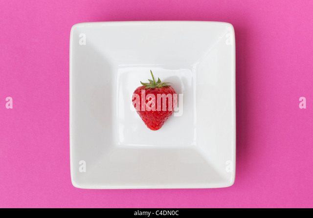 Strawberry in a square ceramic dish on a pink background - Stock Image