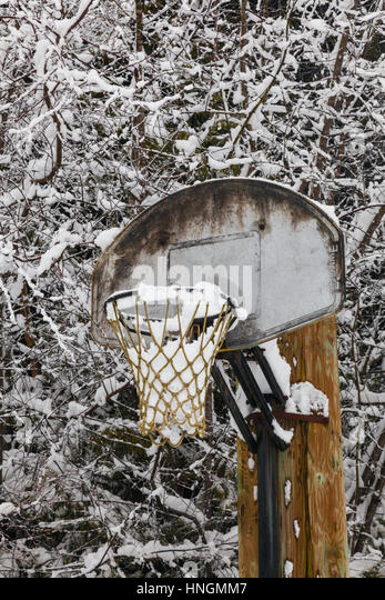 Outdoor basketball net full of snow - Stock Image