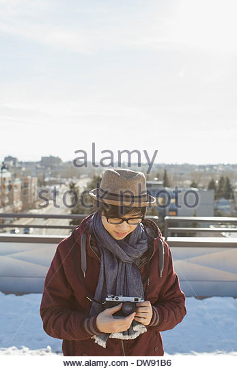 Young man adjusting camera lens on patio - Stock Image