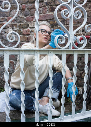 A woman paints her garden gate - Stock Image