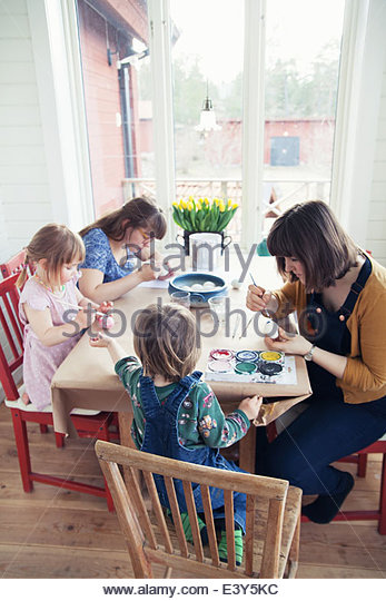 Family painting easter eggs in dining room - Stock Image