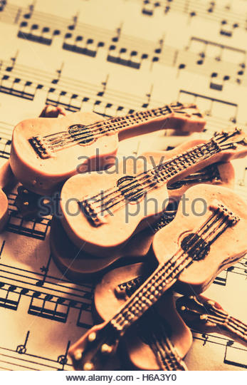 Retro styled still life on a pile of miniature acoustic guitars on lined music background. Retro folk and blues - Stock Image
