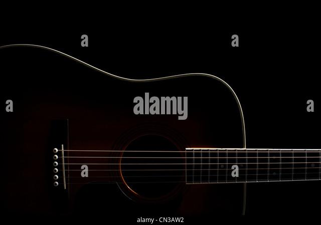 Acoustic guitar against black background - Stock-Bilder