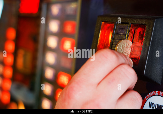 Gambler Inserts pound coin into gambling machine at casino - Stock Image
