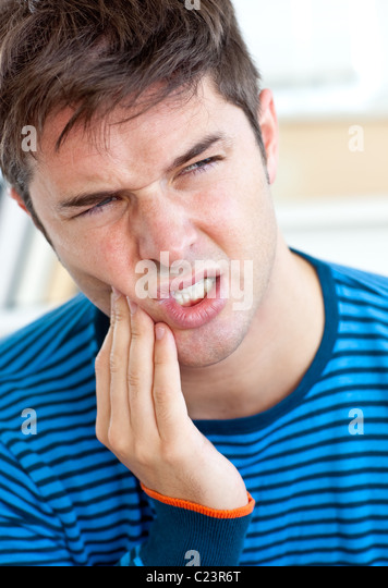 Unhappy man having a toothache in the living-room - Stock Image