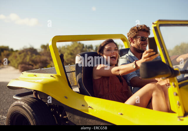 Excited happy couple enjoying road trip in their car. Man driving the car young woman taking a selfie from her mobile - Stock Image