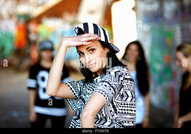 Young woman wearing baseball cap backwards, looking at camera - Stock Image