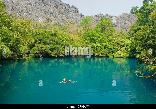 Woman soaking in the clear blue water at Khoun Khong Lang Lagoon near Na Kue village in Laos. - Stock Image