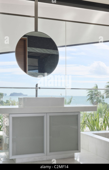 Modern bathroom with round mirror and view from picture windows - Stock Image