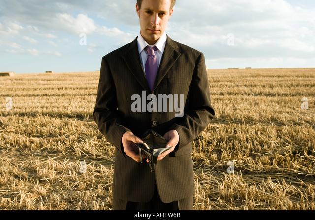 Man holding empty wallet in wheat field. - Stock Image