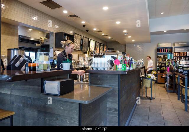 Bradenton Florida Starbucks Coffee coffee company coffeehouse chain salesclerk barista job girl teen patron customer - Stock Image