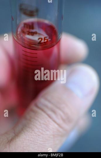 Pink substance in measuring jug - Stock Image