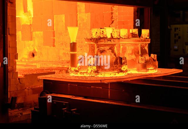 Metal casings glowing in foundry - Stock Image