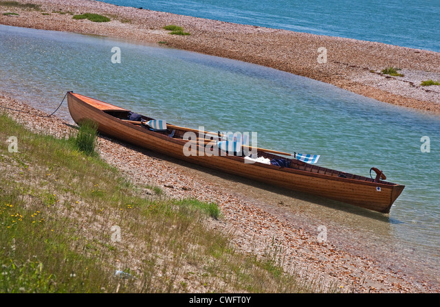 Rowing gig with striped oars - Stock Image
