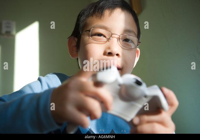 japanese ten year old boy playing video game closeup - Stock-Bilder