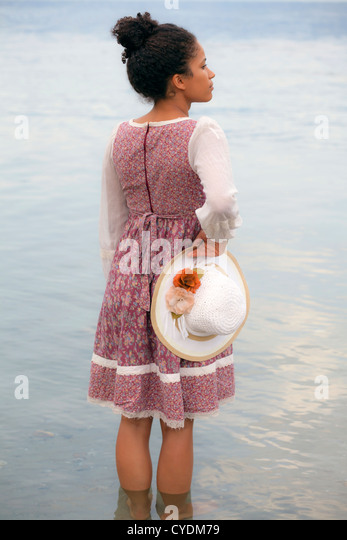 a woman in a floral dress holding a straw hat - Stock Image