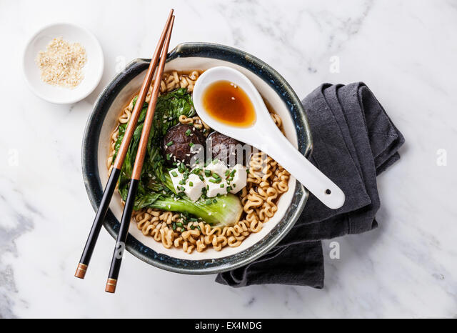 Miso Ramen Asian noodles with shiitake, tofu and cabbage pak choi in bowl on white marble background - Stock Image