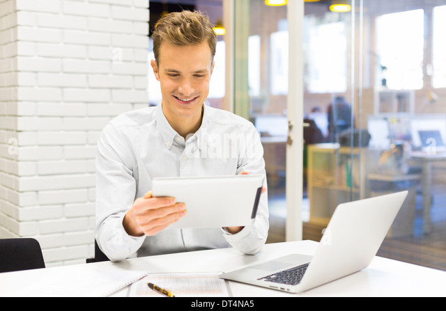 Man business tablet pc desk laptop message e-mail - Stock Image