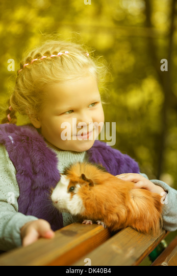 Slyly smiling girl posing with guinea pig - Stock Image