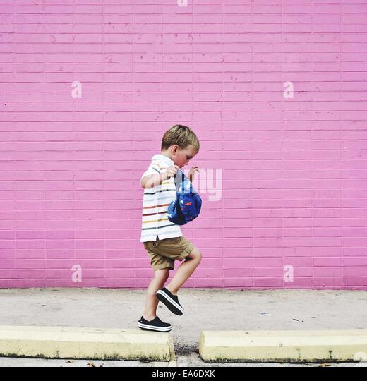 Boy walking along raised sidewalk - Stock Image