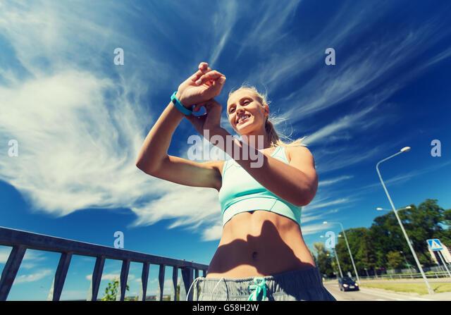 happy woman with heart rate watch and earphones - Stock-Bilder