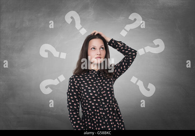 Beautiful woman with questioning expression and question marks above her head - Stock Image