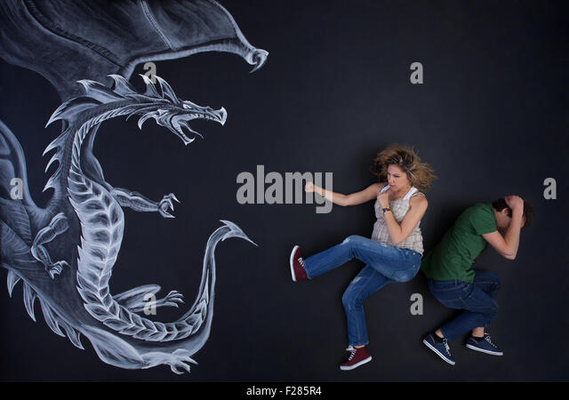 Young pregnant woman protecting his man against a drawing dragon. - Stock-Bilder