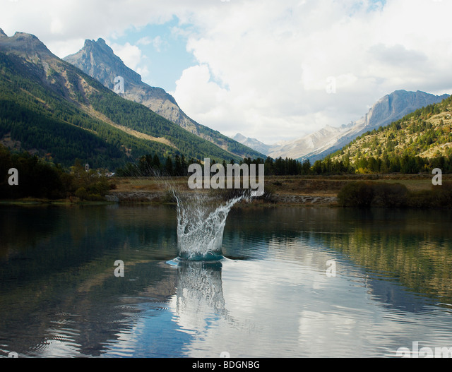 a view of the alps with a lake in the foreground. a splash of water jumping from the lake - Stock Image