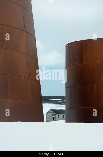 Tall rusting metal whale oil tanks at the former whaling station on Deception Island. - Stock Image