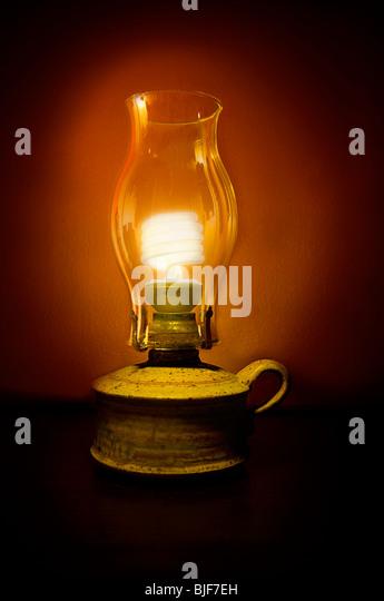 Energy saving sustainability light bulb in oil lamp - Stock Image