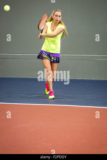 Young woman playing tennis in an indoor tennis center - Stock Image