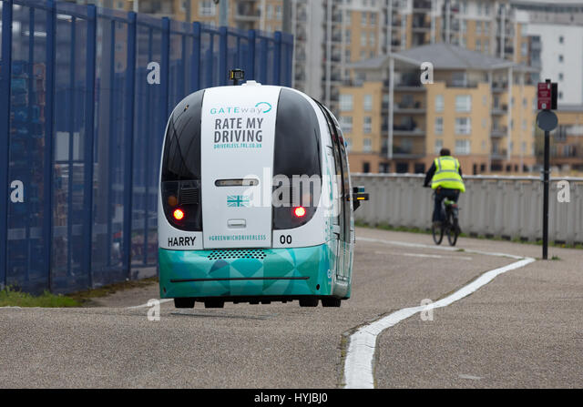 Greenwich, London, UK. 4th April 2017. The driverless vehicle travels along the Thames path next to a cyclist. The - Stock Image
