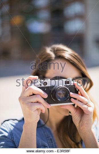 Close up of woman using camera - Stock Image