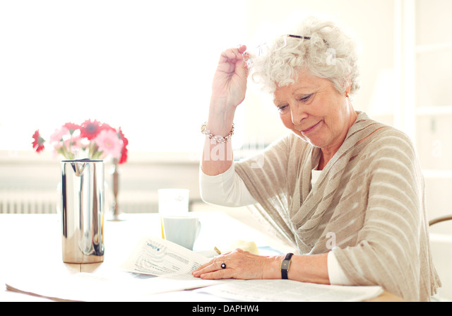 Grandma at home busy reading something - Stock Image