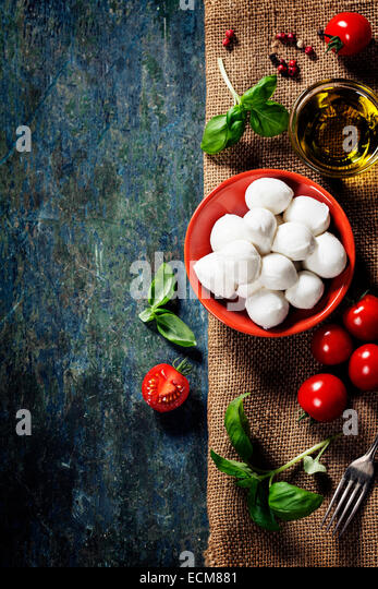 Cherry tomatoes, basil leaves, mozzarella cheese and olive oil for caprese salad. Lots of copy space - Stock Image