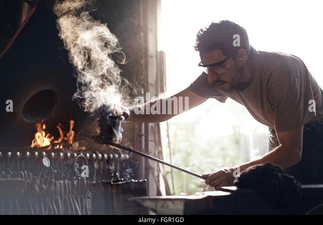 Blacksmith shaping steaming wrought iron in forge - Stock Image