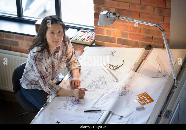 Architect drawing plans at drawing board, portrait - Stock-Bilder