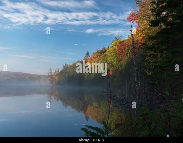 Mist over Smoke lake at dawn. Beautiful fall nature scenery - Stock Image
