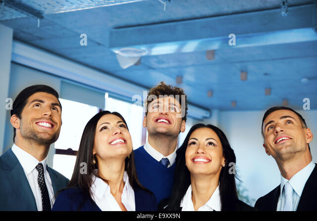 Happy positive business group looking up with dreaming expression - Stock Image