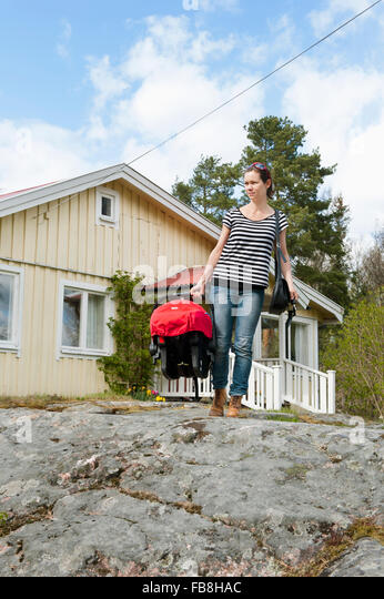 Sweden, Ostergotland, Vikbolandet, Mid-adult woman carrying moses basket with baby girl (6-11 months) - Stock Image